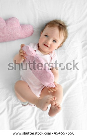 Adorable smiling baby girl on a white sheet - stock photo