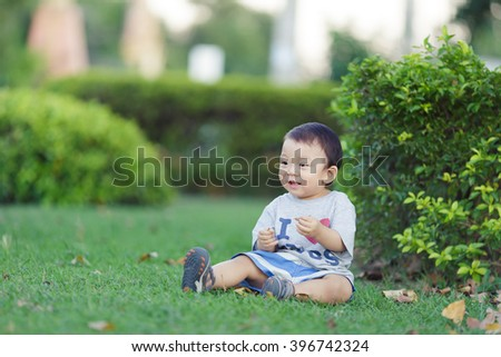 Adorable smiling baby sitting on green grass - stock photo