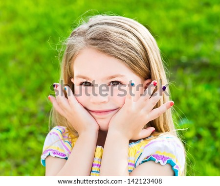 Adorable smiling blond little girl with long hair and many-colored manicure - stock photo
