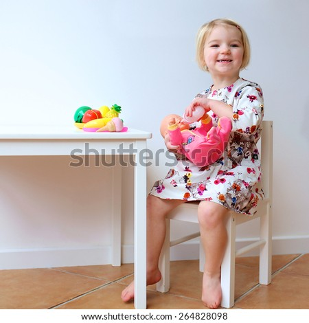 Adorable smiling child, blonde toddler girl wearing beautiful dress playing at home or kindergarten, feeding her doll with toy bottle, plastic fruits and vegetables sitting at white wooden table - stock photo