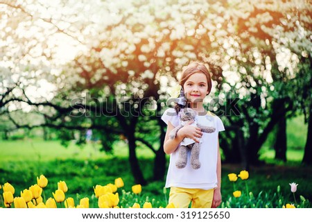 adorable smiling child girl with teddy bear on the walk in spring park with blooming tulips and apple tree on background - stock photo