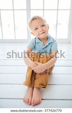 Adorable smiling child sitting on the floor - stock photo