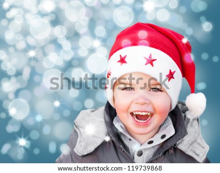 Adorable smiling child wearing Santa Claus christmas hat - stock photo