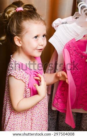 Adorable smiling girl choosing dress - stock photo