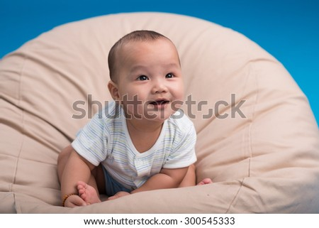 Adorable smiling infant sitting in the armchair and looking up