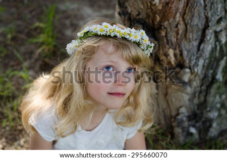 adorable smiling little blond girl with daisy flower headband  - stock photo