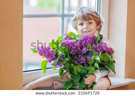 Adorable smiling little boy with blooming purple lilac flowers, indoor. Mother's day, father's day or valentine's day concept. - stock photo