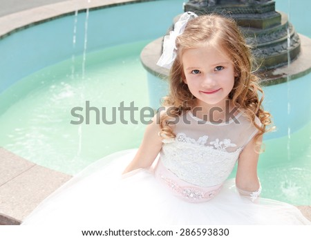 Adorable smiling little girl in princess dress sitting near the fountain outdoor - stock photo