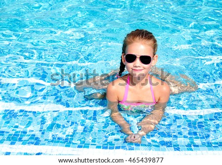 Adorable smiling little girl in swimming pool on vacation