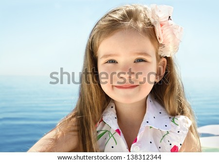 Adorable smiling little girl on beach vacation - stock photo