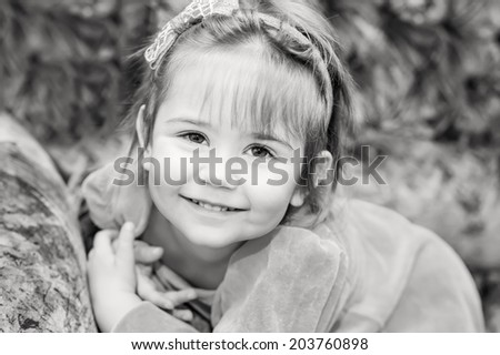 Adorable smiling little girl on the plush sofa  (black and white) - stock photo
