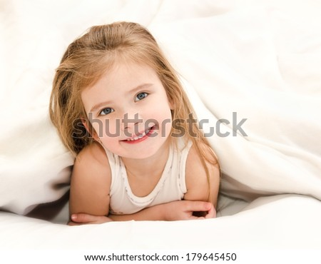 Adorable smiling little girl waked up in her bed