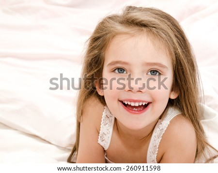 Adorable smiling little girl waked up in her bed  - stock photo