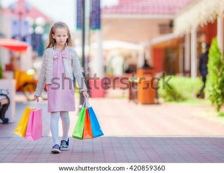 Adorable smiling little girl with shopping bags in big mall - stock photo