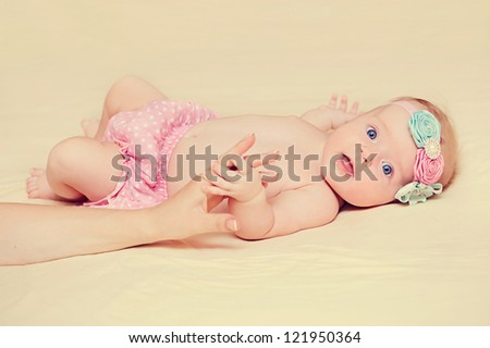 Adorable smiling newborn baby. Little girl holding mother's hand