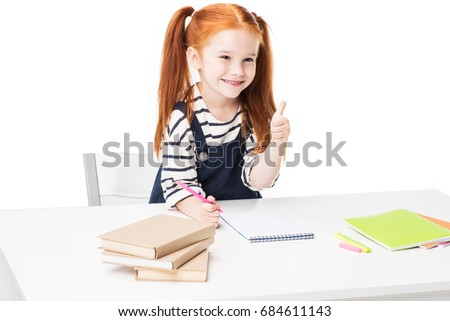 adorable smiling schoolgirl drawing with felt tip pens and showing thumb up isolated on white