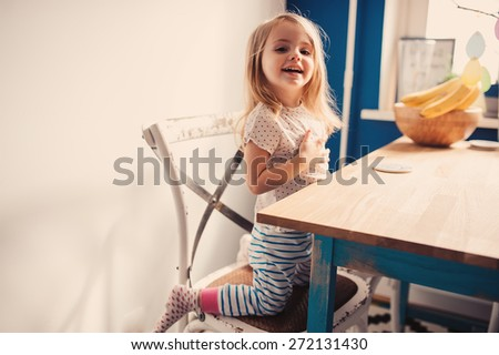 adorable smiling toddler girl having fun at home in the kitchen with vintage interior - stock photo