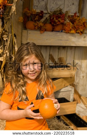 Adorable smiling young girl holding a small pumpkin for Halloween  - stock photo