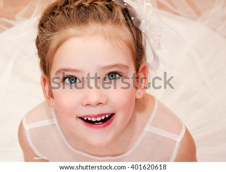 Adorable surprised little girl in princess dress siitting on the floor - stock photo