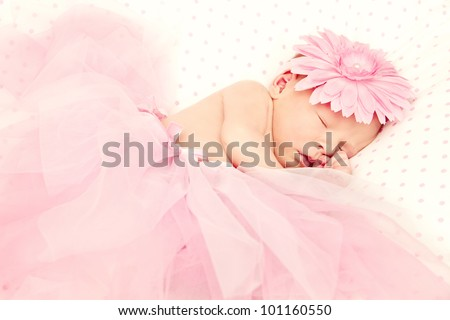 Adorable, sweet ballerina with fluffy pink skirt and flower - stock photo
