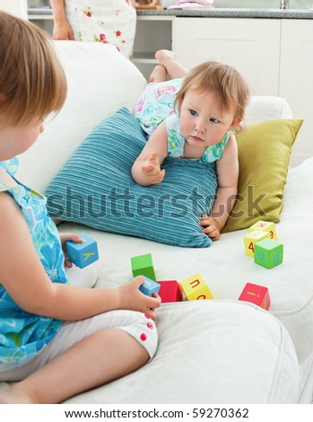 Adorable sweet siblings playing together in the living-room - stock photo