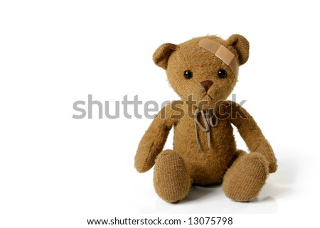 Adorable Teddy Bear with a Bandage on his Head - stock photo