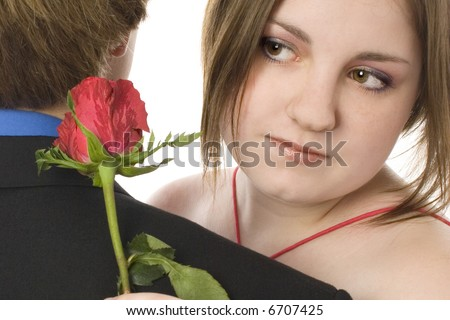 Adorable teen couple in formals with roses.  Prom, dance, Valentine's Day or Christmas.  Close-up dancing. - stock photo