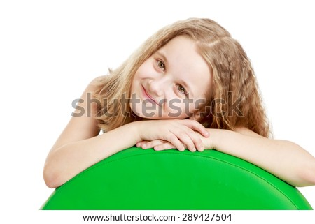Adorable teen girl laid her hands on a big ball-Isolated on white background - stock photo