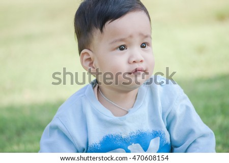 Adorable ten month baby boy in bright blue suit sit on green grass meadow, he feel happy and comfortable.