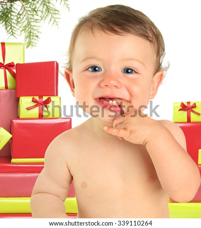 Adorable ten month old baby boy surrounded by Christmas gifts.