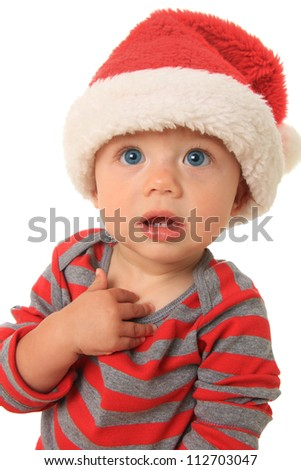 Adorable ten month old baby boy wearing a Santa hat.