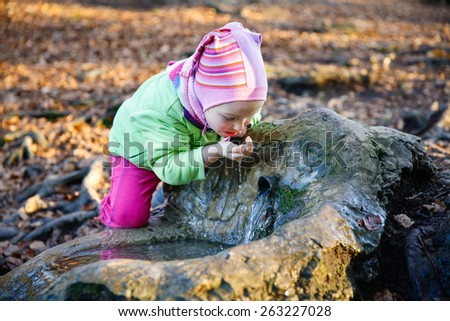 Adorable, thirsty little girl drinking clean spring water from a source in a forest - stock photo