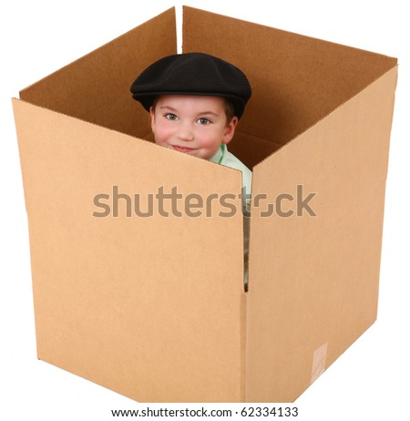 Adorable three year old boy with hat in a cardboard box over white background.