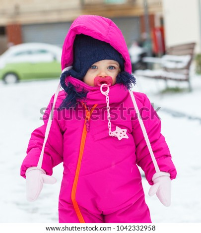 Adorable toddler baby girl in a magenta snow suit playing on the snow.