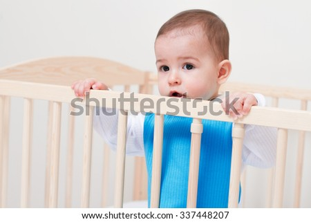 Adorable toddler baby sitting on the white bed