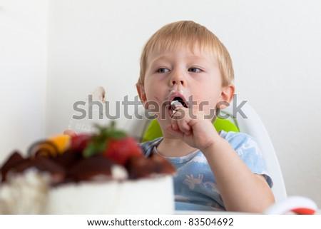 Adorable toddler boy eating cake - stock photo
