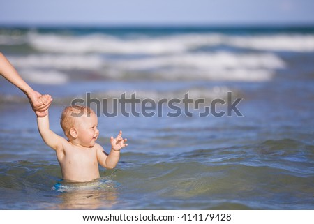 Adorable toddler boy enjoying swimming in the ocean on a sunny day. Mother and child in the sea. Family on vacations. Little child in water, outdoors. - stock photo