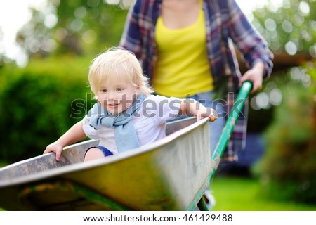 Adorable toddler boy having fun in a wheelbarrow pushing by mum in domestic garden, on warm sunny day. Active outdoors games for kids in summer.