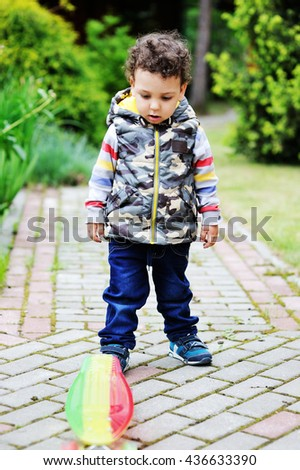 Adorable toddler boy having fun with colorful skateboard outdoors in the park - stock photo