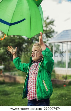 Adorable toddler boy play with green umbrella. Outdoors portrait - stock photo