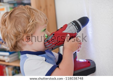 Adorable toddler boy playing with drill at home