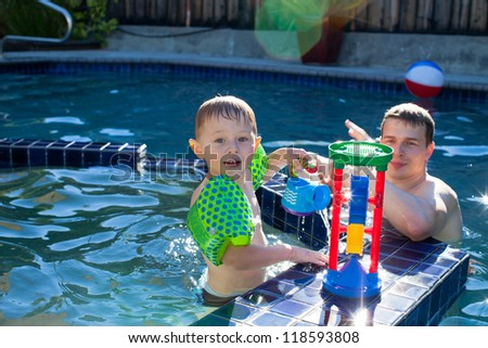Adorable toddler boy playing with his father in the pool - stock photo