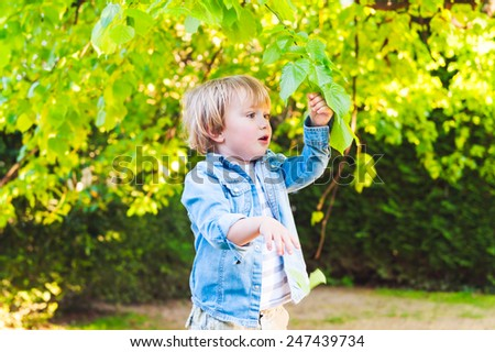 Adorable toddler boy playing with leaves in a park on a nice summer day - stock photo