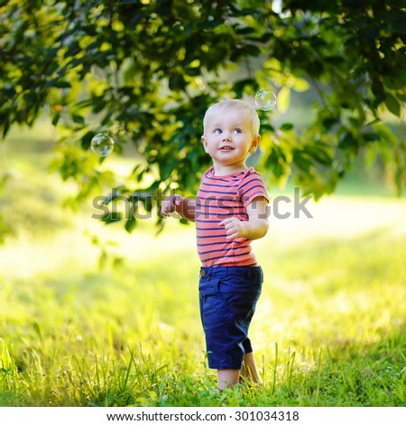 Adorable toddler boy playing with soap bubbles outdoors - stock photo