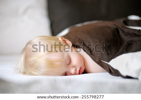 Adorable toddler boy sleeping in a bed