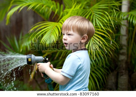 Adorable toddler boy watering plants in the garden