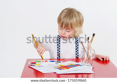 Adorable toddler drawing with colorful water painting