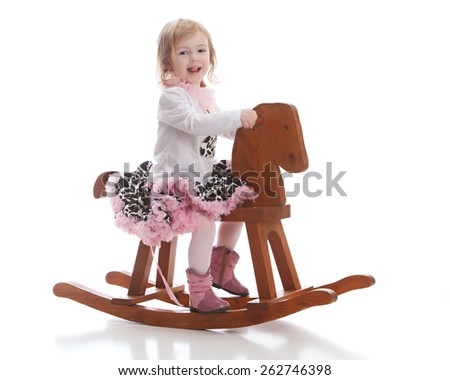 Adorable toddler dressed in a  shirt with a number 2 on it, a spotted skirt, and cowboy boots riding a rocking horse.  Isolated on white. - stock photo