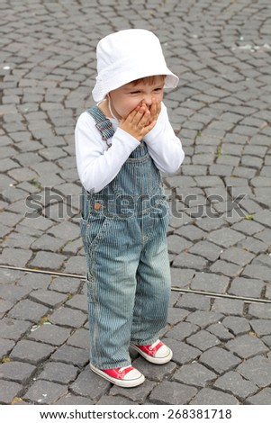 Adorable toddler giggles while walking the pedestrian street - stock photo