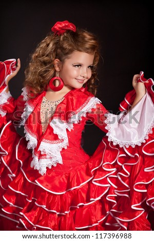 Adorable toddler girl dancing flamenco in traditional spanish red dress. Little child  from Andalusia with curly hair dancing Gypsy dance. Portrait of trendy artist baby in carnival latin costume. - stock photo